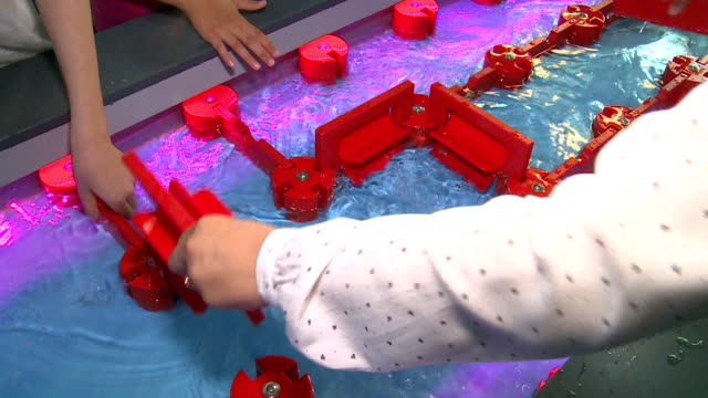 Hands play with water mills constructor in expo 2017. video