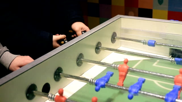 Hands playing table football video