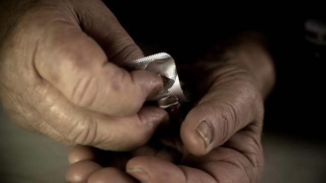 stockvideo's en b-roll-footage met hd: hands pops a pill from the blister pack - doordrukstrip