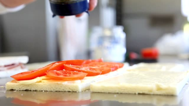 hands prepare a cheese and tomato sandwich video