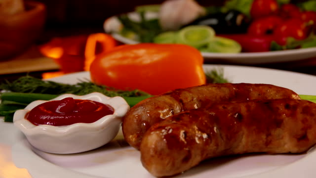 Hands put a plate of dinner with grilled sausage video