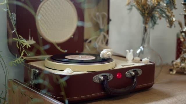 mani che mettono un disco in vinile su un lettore, pan shot - disco audio analogico video stock e b–roll