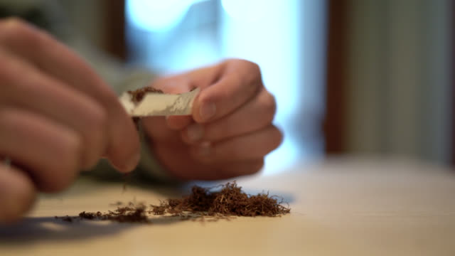 Hands rolling cigarette paper with tobacco Hands rolling cigarette paper with tobacco hashish stock videos & royalty-free footage