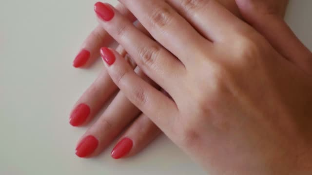 hands showing fresh red manicure at the nail salon - ноготь на руке стоковые видео и кадры b-roll