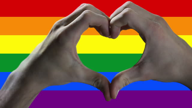 Hands showing Heart Sign over a Gay Pride Flag.