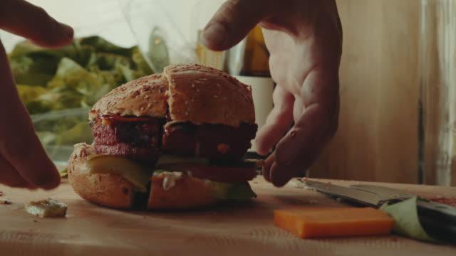 vídeos de stock e filmes b-roll de hands showing the inside of a plant based, non-meat, vegan burger - meat texture