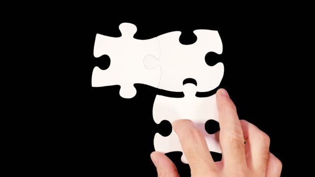 Hands solving a puzzle. Black background. Luma Matte. video