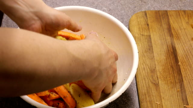 Hands stir potatoes and carrots with olive oil and spices. video