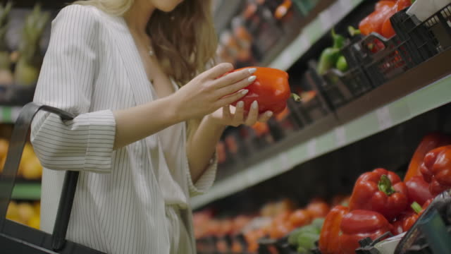 Hands take few colorful pepper one by one in marketplace and hold. Close up concept of selection, buy quality fruit or red vegetables. Young woman pick up some tasty freshness ingredient for cooking.