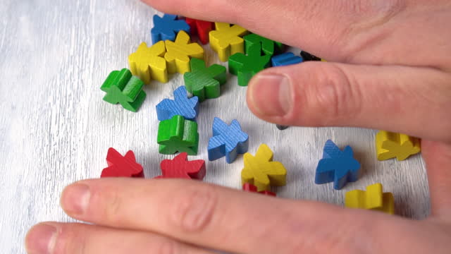 Hands take multi-colored wooden figures on the board