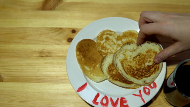Hands take pancakes in the shape of heart with a white plate. video