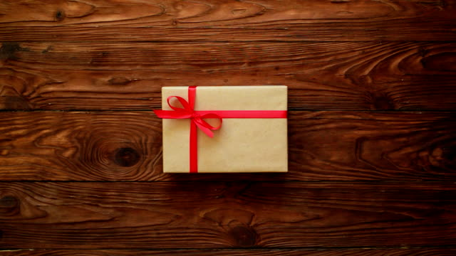 Hands taking away a gift box from the wooden background video
