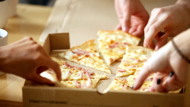 Hands taking pieces of sliced pizza from open box, closeup video