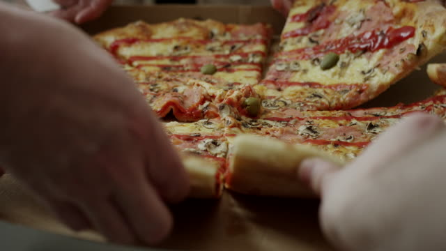 vídeos de stock e filmes b-roll de hands taking pizza slices out or box - pizza