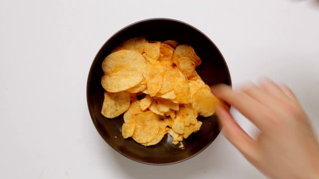 Hands Taking Potato Chips from Bowl Hands taking potato chips from bowl until them runs out! snack stock videos & royalty-free footage