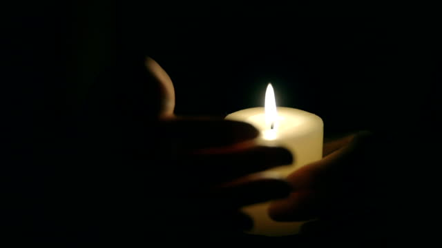 Hands that protect the flame of a candle Hands that protect the flame of a candle candle stock videos & royalty-free footage