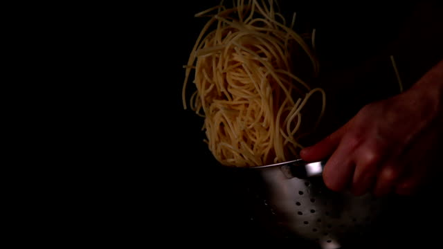 Hands tossing spaghetti in colander video