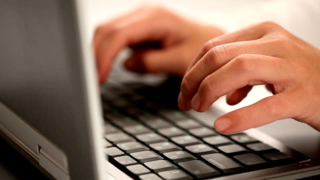 Hands typing on a laptop keyboard video