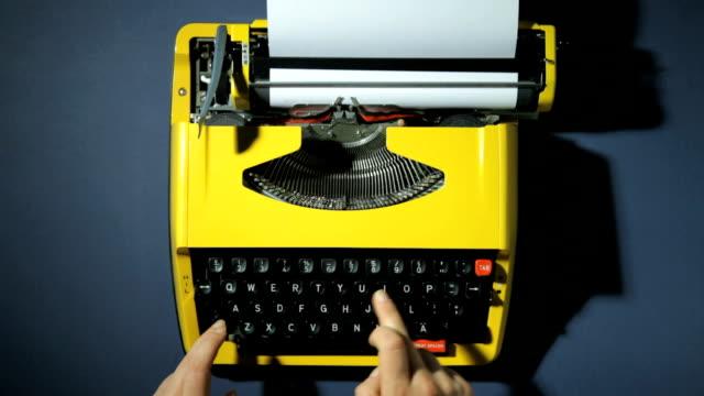 Hands typing on typewriter Hands typing on yellow typewriter typewriter stock videos & royalty-free footage
