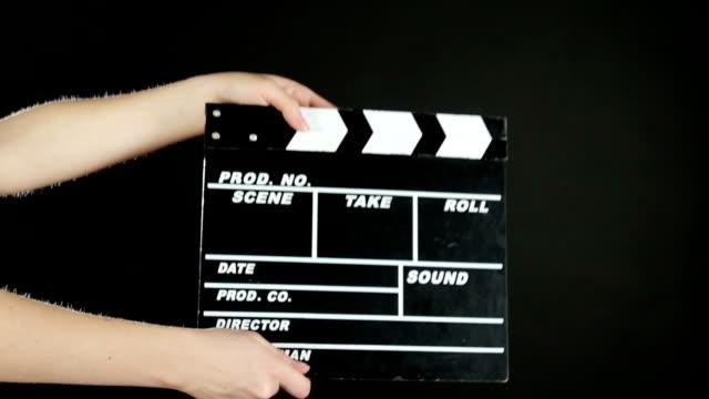 vidéos et rushes de mains utiliser la production de film clapper conseil, sur noir, au ralenti - ardoise