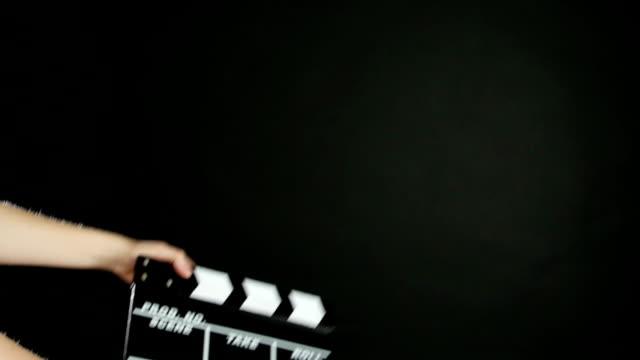 vidéos et rushes de mains utiliser la production de film clapper conseil, sur noir - ardoise