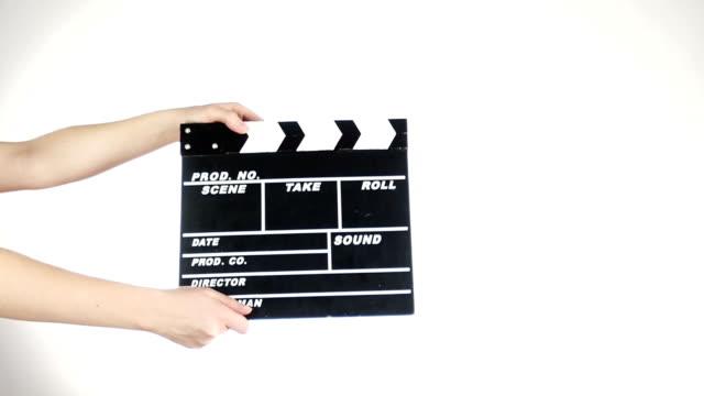 vidéos et rushes de mains utiliser la production de film clapper conseil, sur fond blanc, au ralenti - ardoise