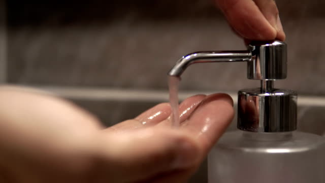 Hands using wash hand sanitizer gel pump dispenser, cinematic dof video