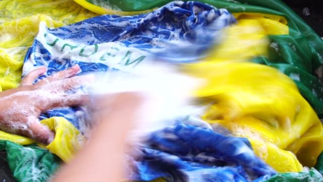 händer tvätt brasilianska flaggan - nytt brasilien/korruption koncept - dirty money bildbanksvideor och videomaterial från bakom kulisserna