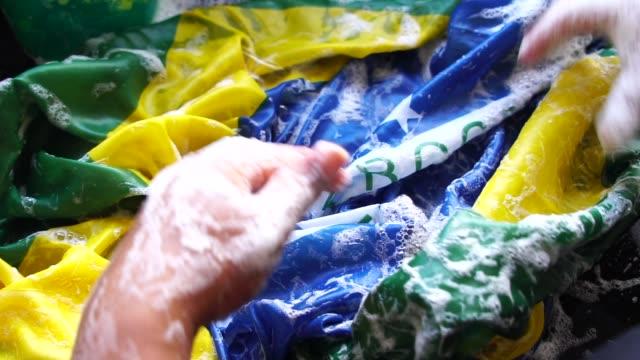 vídeos de stock e filmes b-roll de hands washing brazilian flag - new brazil/corruption concept - corruption