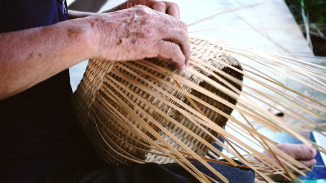 hands weaving bamboo basket, handmade by villagers from chiangmai, thailand. - prodotto d'artigianato video stock e b–roll