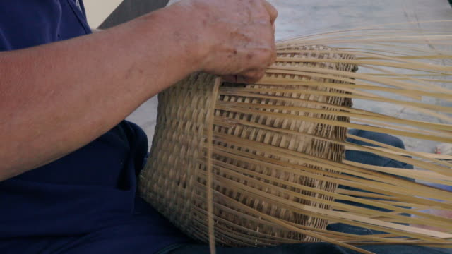 hands weaving bamboo basket, handmade by villagers from chiangmai, thailand. - тростник стоковые видео и кадры b-roll