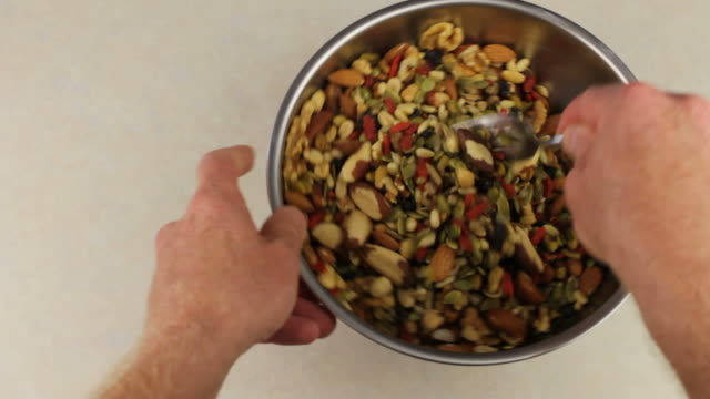 Hands With Fork Mixing Nuts And Fruits Mix video