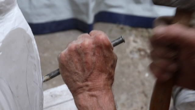 Hands with hammer and chisel