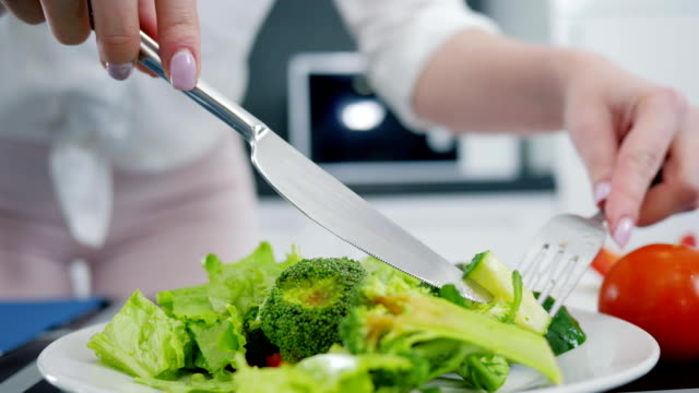 hands with knife and fork mix fresh organic green salad in kitchen, lettuce with broccoli and cucumber hands with knife and fork mix fresh organic green salad in the kitchen, lettuce with broccoli and cucumber salad bowl stock videos & royalty-free footage