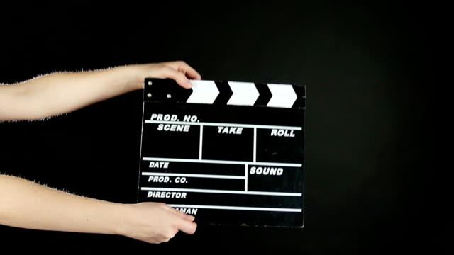 vidéos et rushes de mains avec cinéma clapper conseil de production, sur noir, au ralenti - ardoise