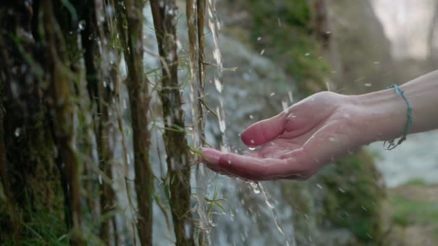 純粋な泉の水を手に。透き通った山の水 - 手 女性点の映像素材/bロール