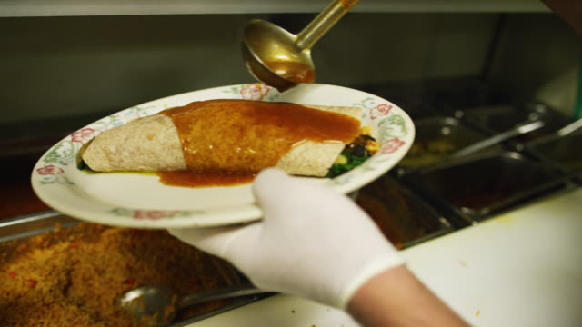 Hands with Rubber Gloves Pour Enchilada Sauce on Burrito with Spinach in a Commercial Kitchen at a Mexican Restaurant