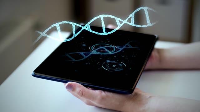 タブレット pc と dna の仮想ホログラムで手 - 鎖の輪点の映像素材/bロール