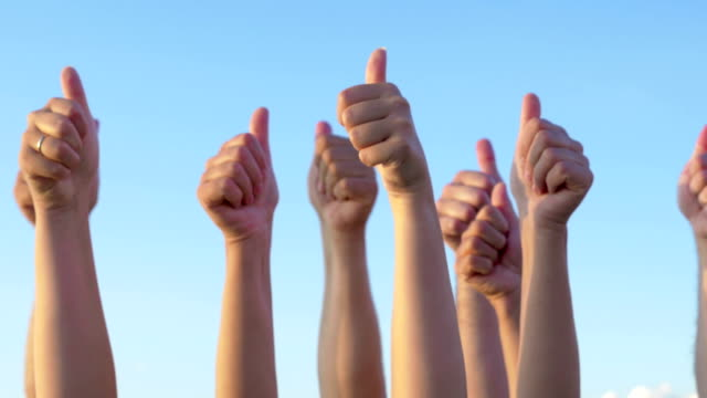 Hands with thumbs up raised against blue sky video