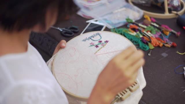 vidéos et rushes de mains femme brode fleurs sur le cerceau, fait à la main et le concept artisanal. - coudre
