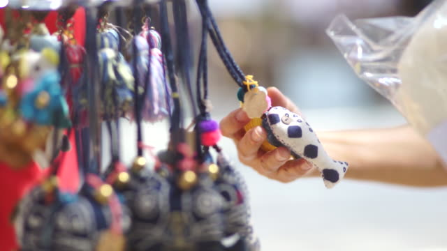 Hand's women with patchwork keychain souvenirs from craft product market , handmade and handicraft concept.