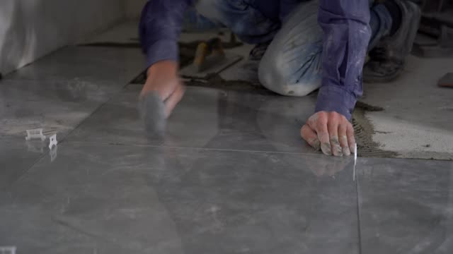 Hands working placing ceramic floor tiles