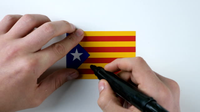 Hands writes NO on the Catalan flag video