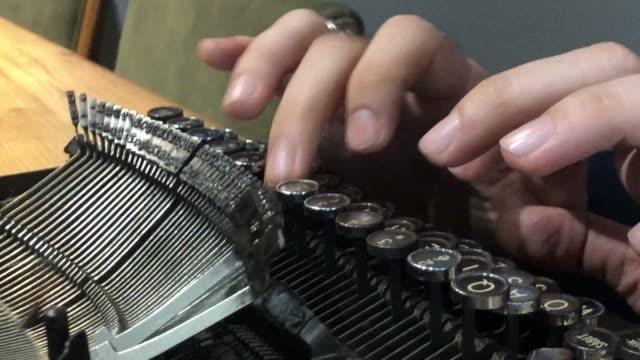 Hands writing on old typewriter.