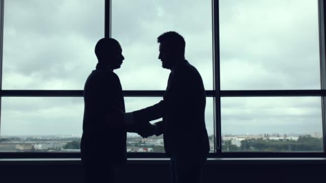 vidéos et rushes de poignée de main contre la vitre. - costume habillé