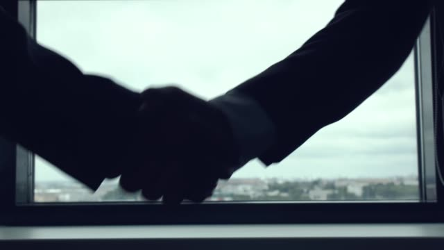 Handshake against the window. Silhouette handshake of two businessmen against the background of large window. Consolidation of the agreement, union, contract, negotiations by shaking handshake. Handshake against the window. shaking stock videos & royalty-free footage