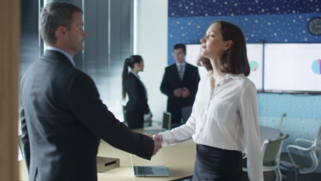 handshake between male manager and female office worker - direttrice video stock e b–roll