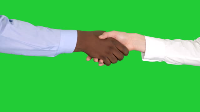 Handshake of Afro American and caucasian female hands on a Green Screen, Chroma Key