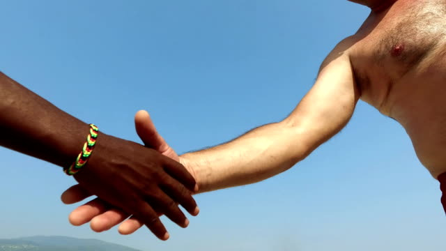 Handshake of two unrecognizable black and white men on blue sky. close up view. Equality video