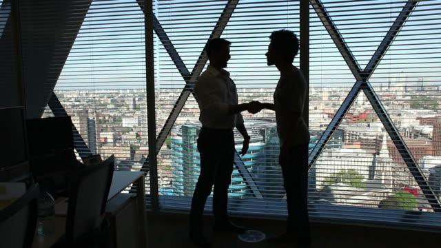 Handshake overlooking skyscrapers video